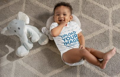 Onesie Mockup of a Sweet Baby Boy with Dimples Next to His Stuffed Toys 25115