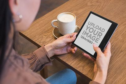 Mockup of a Woman Holding a Kindle Oasis While Sitting at a Cafe 26021
