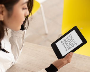 Mockup of a Woman on a Table Reading Her Kindle Paperwhite 26152