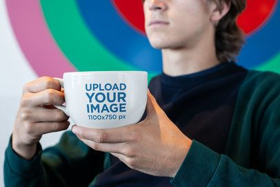 Coffee Mug Mockup of a Man Sitting in Front of a Colorful Wall 26513