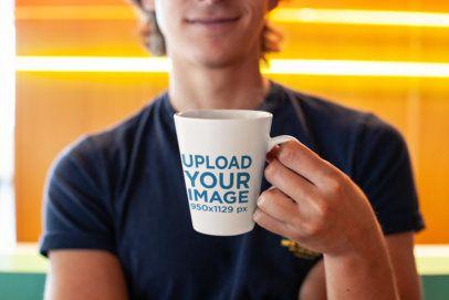 Mockup of a Smiling Young Man Holding an 11 oz Coffee Mug 26518
