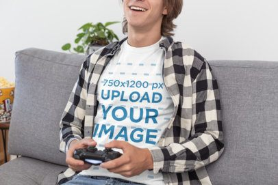 T-Shirt Mockup of a Young Man Happily Playing Video Games in His Living Room 26900
