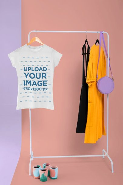 Mockup of a  Women's T-Shirt Hanging from a Rack Next to a Couple of Dresses 26726