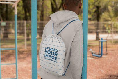Drawstring Bag Mockup of a Man at a Park Facing Backward 27583