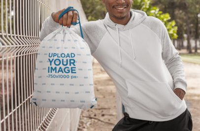 Drawstring Bag Mockup Featuring a Man Leaning Against a Wire Fence 27588