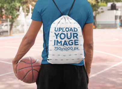Mockup of a Man With a Drawstring Bag in a Basketball Court 27592