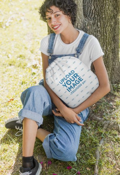 Mockup Featuring a Woman Holding a Drawstring Bag Sitting Under a Tree 27598