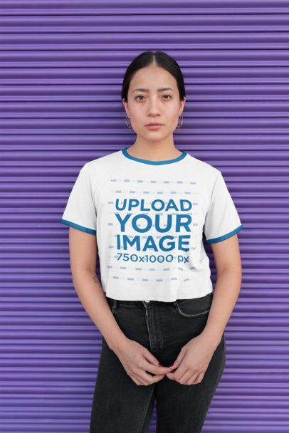 Mockup of a Woman Wearing a Ringer T-Shirt Against a Roller Door 27172