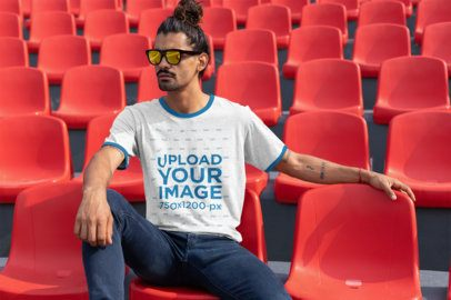 Ringer Tee Mockup of a Man with a Hair Bun Sitting on a Red Stadium Seat 27901
