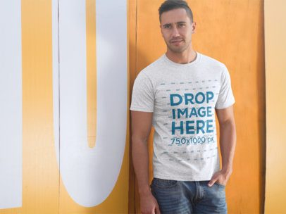 T-Shirt Mockup of a Man Standing Against a Yellow Door a8670
