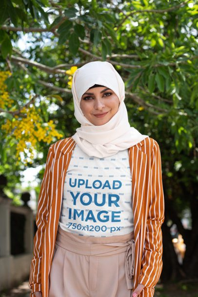 T-Shirt Mockup of a Woman with a Hijab Posing Under a Tree 28294