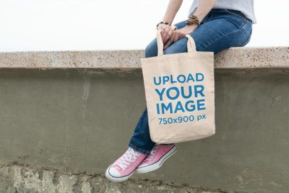 Tote Bag Mockup Featuring a Young Woman Sitting on a Wall 104-el