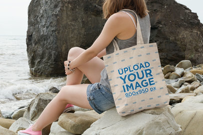 Tote Bag Mockup Featuring a Young Woman Sitting on a Rock by the Sea 109 -el