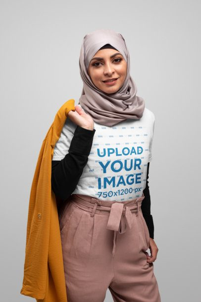 T-Shirt Mockup Featuring a Woman with a Hijab Carrying a Coat over Her Shoulder 28288