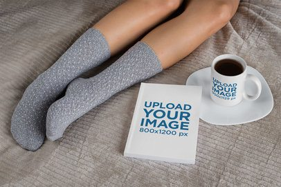 Mockup of an 11 oz Mug and a Book on a Bed 28468