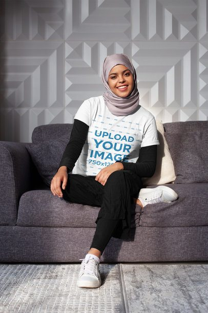 T-Shirt Mockup of a Woman with a Hijab Sitting with One Leg Crossed 28401