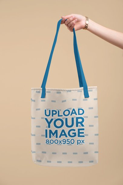 Mockup of a Hand Holding a Customizable Strap Tote Bag Against a Flat Surface 28832