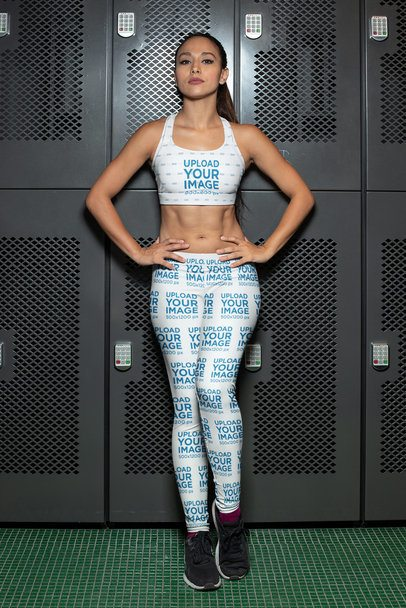 Sports Bra Mockup of a Woman Wearing Leggings and Posing Against Some Gym Lockers 28694