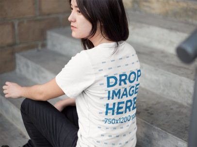 Back of an Asian Girl Wearing a Round Neck T-Shirt Mockup Sitting on a Stairway a9536b