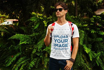 V-Neck T-Shirt Mockup Featuring a Young Man Standing in Front of Some Fern Bushes 512-el