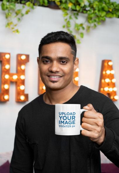 11 oz Coffee Mug Mockup of a Young Smiling Man in Front of a Marquee Sign 28967