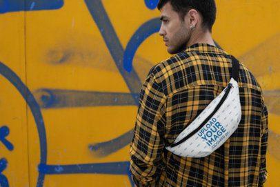 Mockup of a Man Wearing a Fanny Pack Facing a Wall with Graffiti  29181