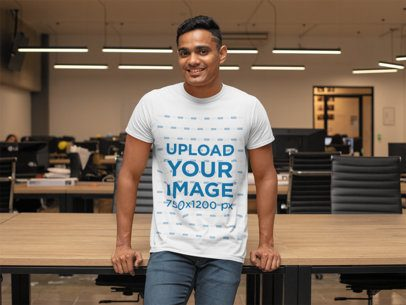 T-Shirt Mockup Featuring a Smiling Man Leaning on a Desk at the Office 28959
