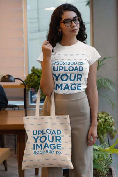 T-Shirt Mockup of a Woman Holding a Tote Bag at an Office 29413