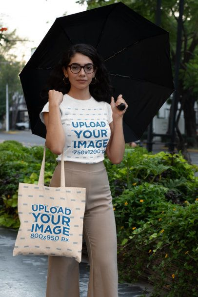 T-Shirt Mockup of a Woman with a Tote Bag on a Rainy Day 29414