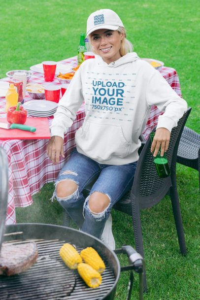 Mockup of a Woman Wearing a Dad Hat and a Pullover Hoodie at a BBQ Backyard Party 29721