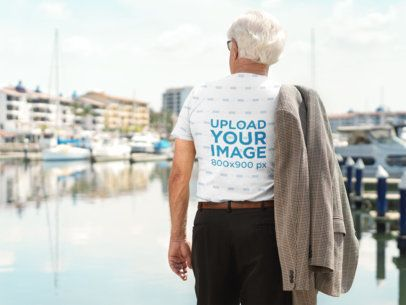 Mockup of the Back of an Elder Man Wearing a Sublimated Tee on a Deck a10932b