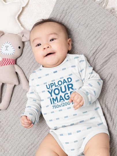 Sublimated Onesie Mockup Featuring a Baby Lying Next to a Toy 30018