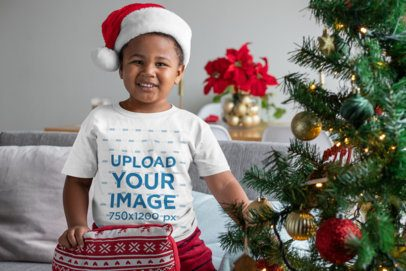 T-Shirt Mockup of a Kid Holding an Ugly Christmas Cushion 30363