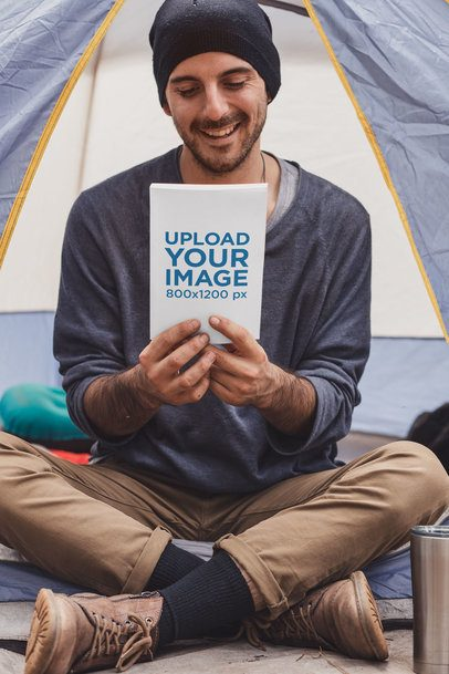 Book Mockup Featuring a Joyful Man Sitting in a Camping Tent 30479