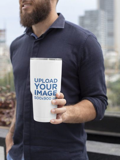 Mockup of a Bearded Man Holding a 30 oz Travel Mug in the City 30375