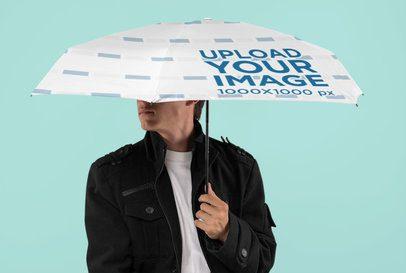 Mockup of a Man Holding an Umbrella at a Studio 30716