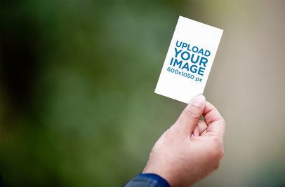 Mockup of a Hand Holding a Vertical Business Card by the Corner 1651-el