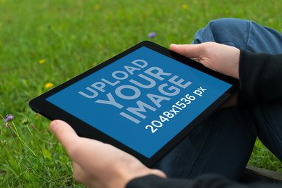 Mockup Featuring a Man Holding an iPad Mini While Sitting on the Grass 2053-el1