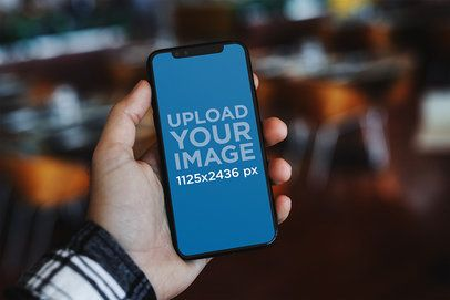 Mockup of a Man Holding an iPhone 11 Pro Against a Blurry Background 2124-el1