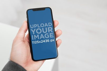 iPhone 11 Pro Mockup Featuring a Man in a Minimalist Room 2152-el1