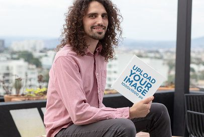 Mockup of a Smiling Man Holding a Square Hardcover Book 30928