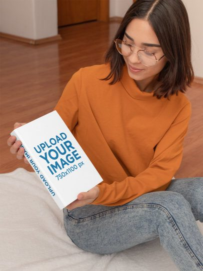 Mockup of a Woman Holding a Hardcover Book at Home 31041