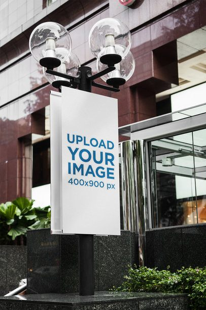 Mockup of a Banner Sign Attached to a Post Outside a Building 2305-el1