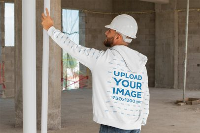 Mockup of a Man Wearing a Hoodie and Working on a Construction 31540