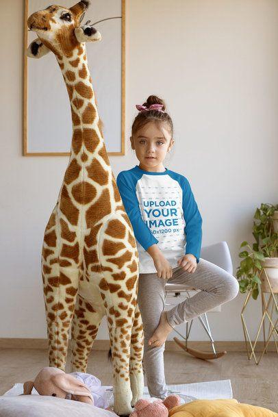 Raglan T-Shirt Mockup Featuring a Little Girl Standing by a Big Stuffed Giraffe 31688
