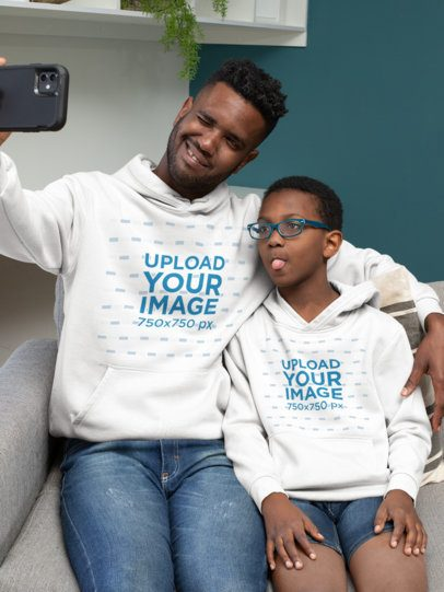 Mockup of a Dad and Kid with Hoodies Taking a Selfie 33113