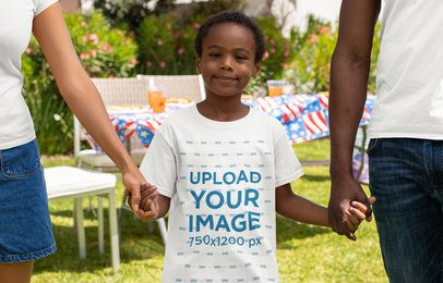 T-Shirt Mockup of a Boy Holding His Parent's Hands at a 4th of July Celebration Party 33015