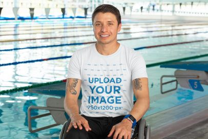 T-Shirt Mockup of a Tattooed Man Using a Wheelchair Next to a Pool 32483