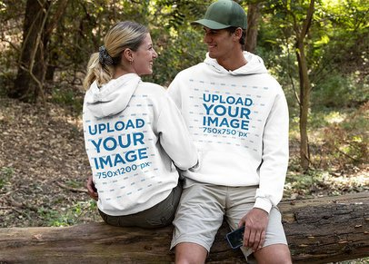 Hoodie Mockup of a Couple Sitting Together in the Woods 32224