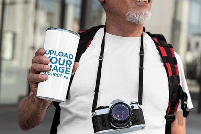 Mockup of a Senior Man Holding a 20 oz Travel Mug 32892